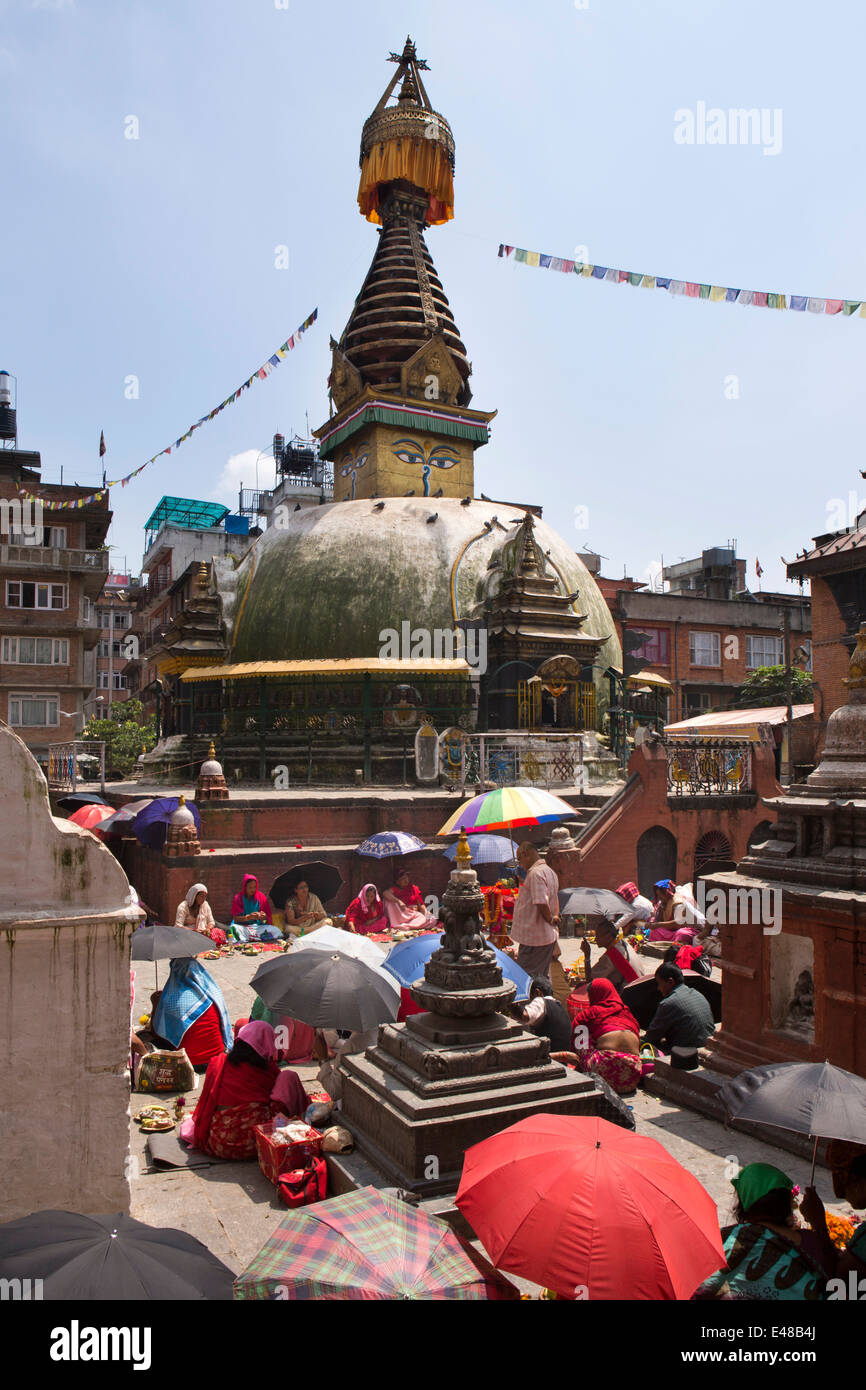 Nepal, Kathmandu, Kathesimbhu Stupa,Tibetan woman undertaking ritual Buddhist puja under parasols - Stock Image