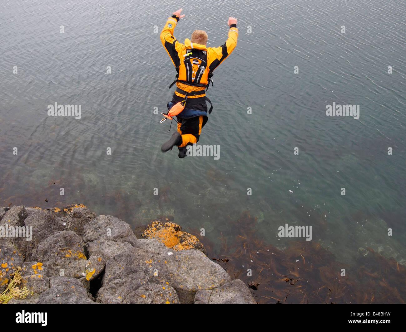 leaping off cliff, Ögurnes near Suðavík, west fjords, Iceland - Stock Image