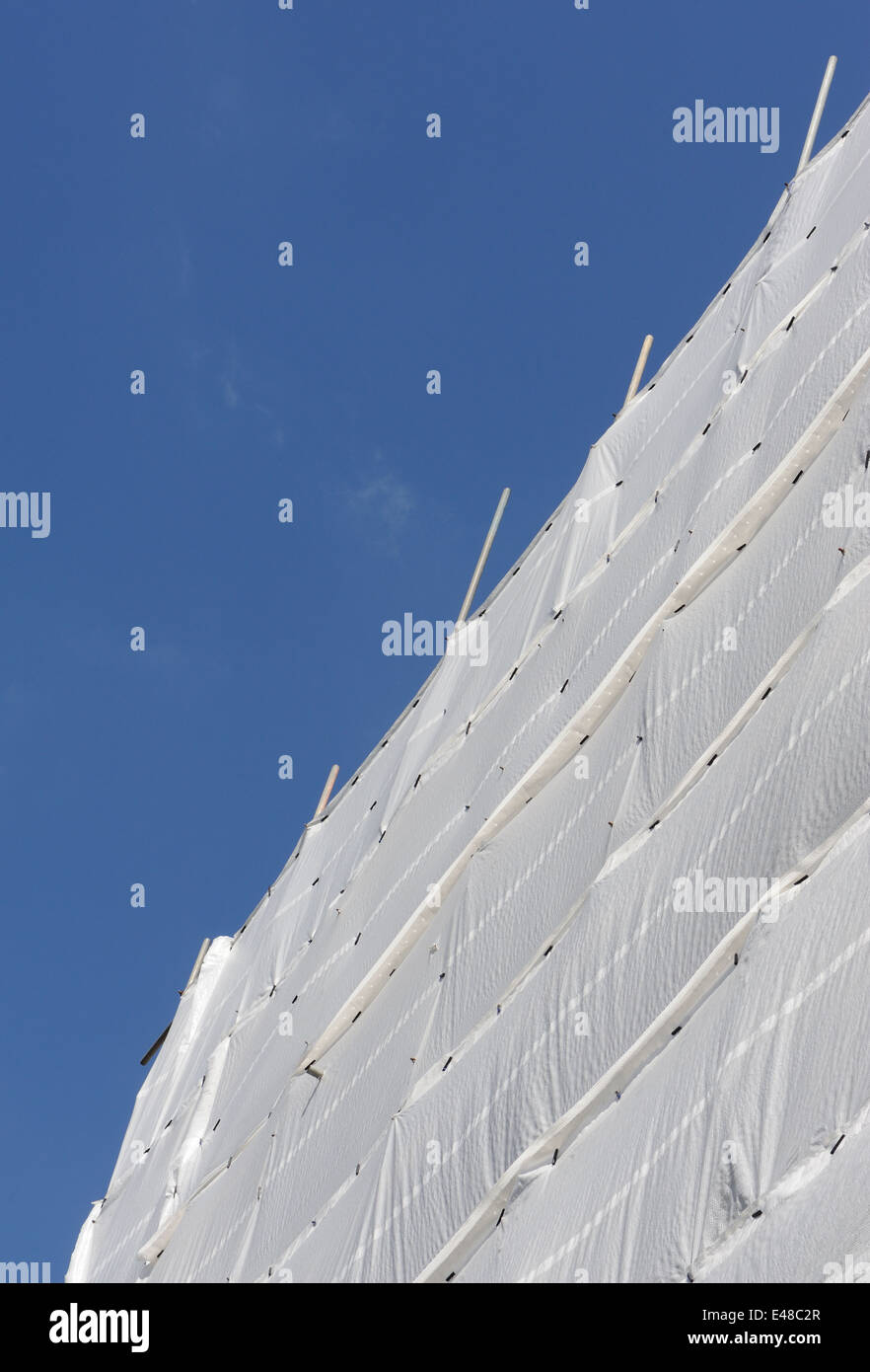 White plastic sheeting covers scaffolding on a building site. City of London, UK. - Stock Image