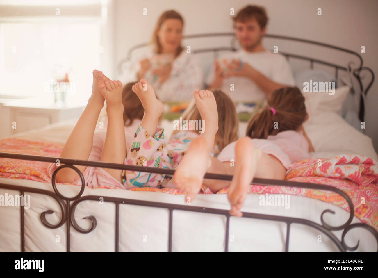 Girls (4-5, 6-7) lying in parent's bed while mother and father are eating breakfast Stock Photo