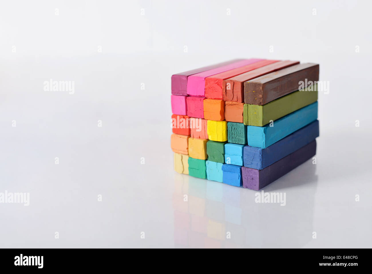 The cube from multicolored artist's pastels on light background - Stock Image