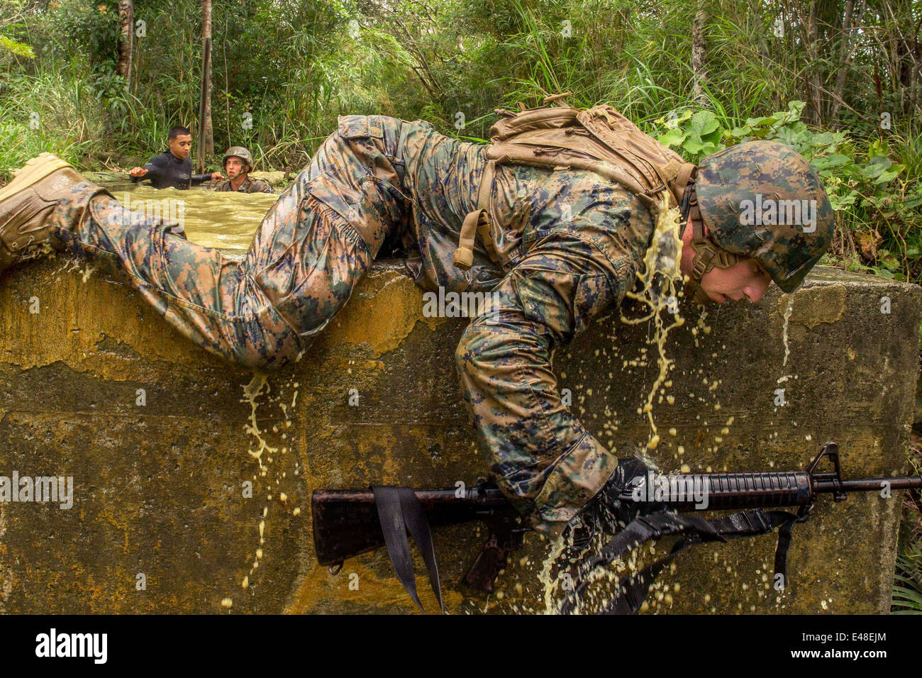 A US Marine crawls over a stone wall during the jungle endurance course at the Jungle Warfare Training Center at - Stock Image