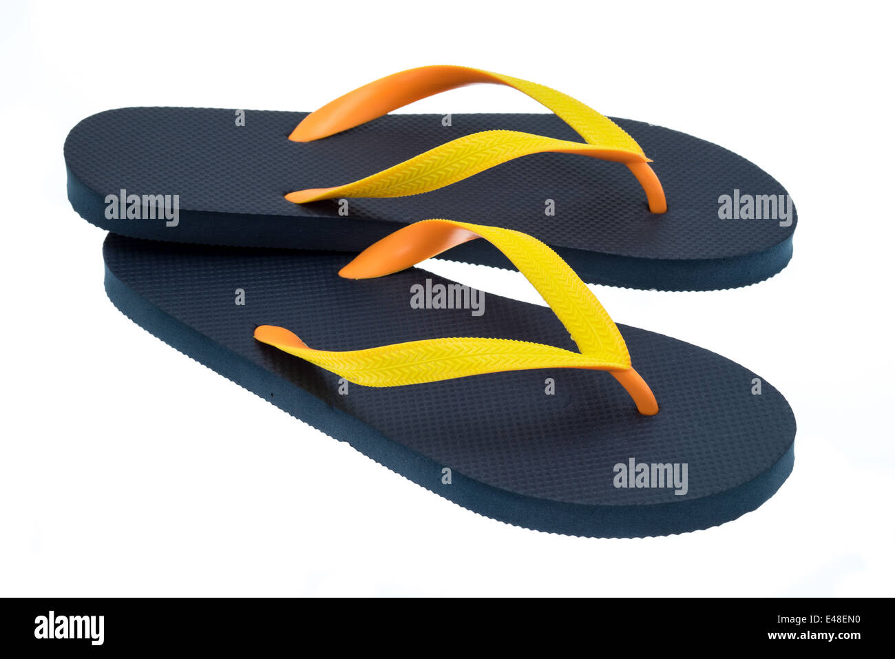 58e213604378d Black thong type flip-flops with orange and yellow straps - studio shot  with a white background