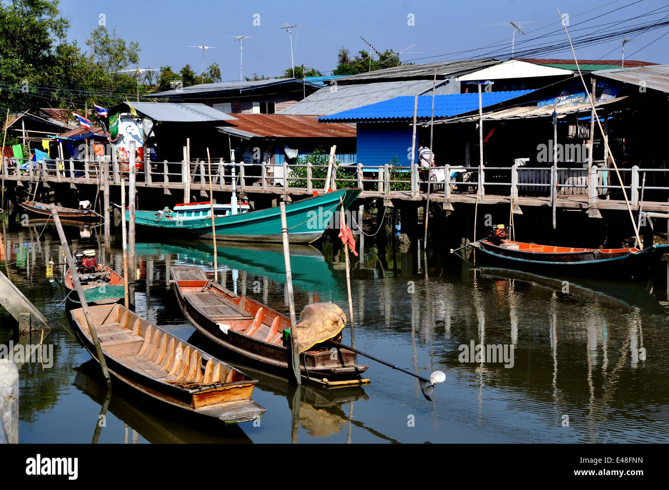 SAMUT SONGKHRAM, THAILAND: Old wooden fishing boats moored to walkways - Stock Image