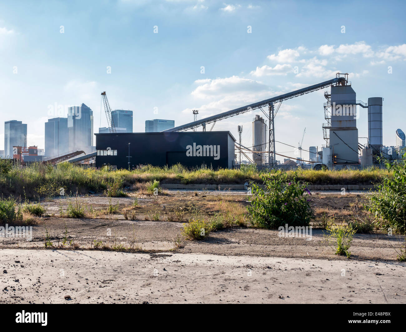 Urban Wasteland and cement works of Greenwich Peninsula and Canary Wharf skyline -  London, UK - Stock Image