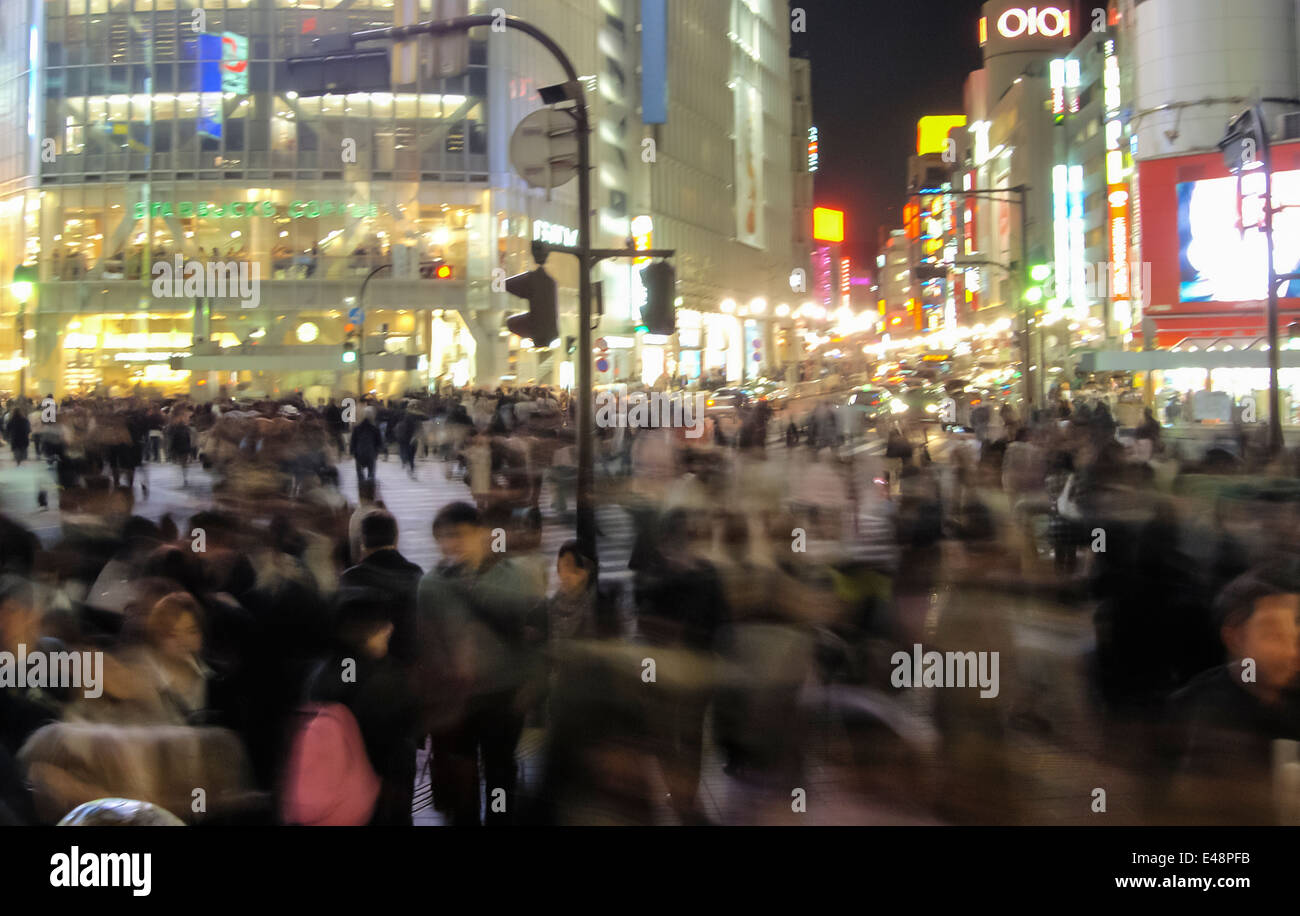 Pedestrians are crossing the Shibuya crossroads in Tokyo, Japan, at night. - Stock Image