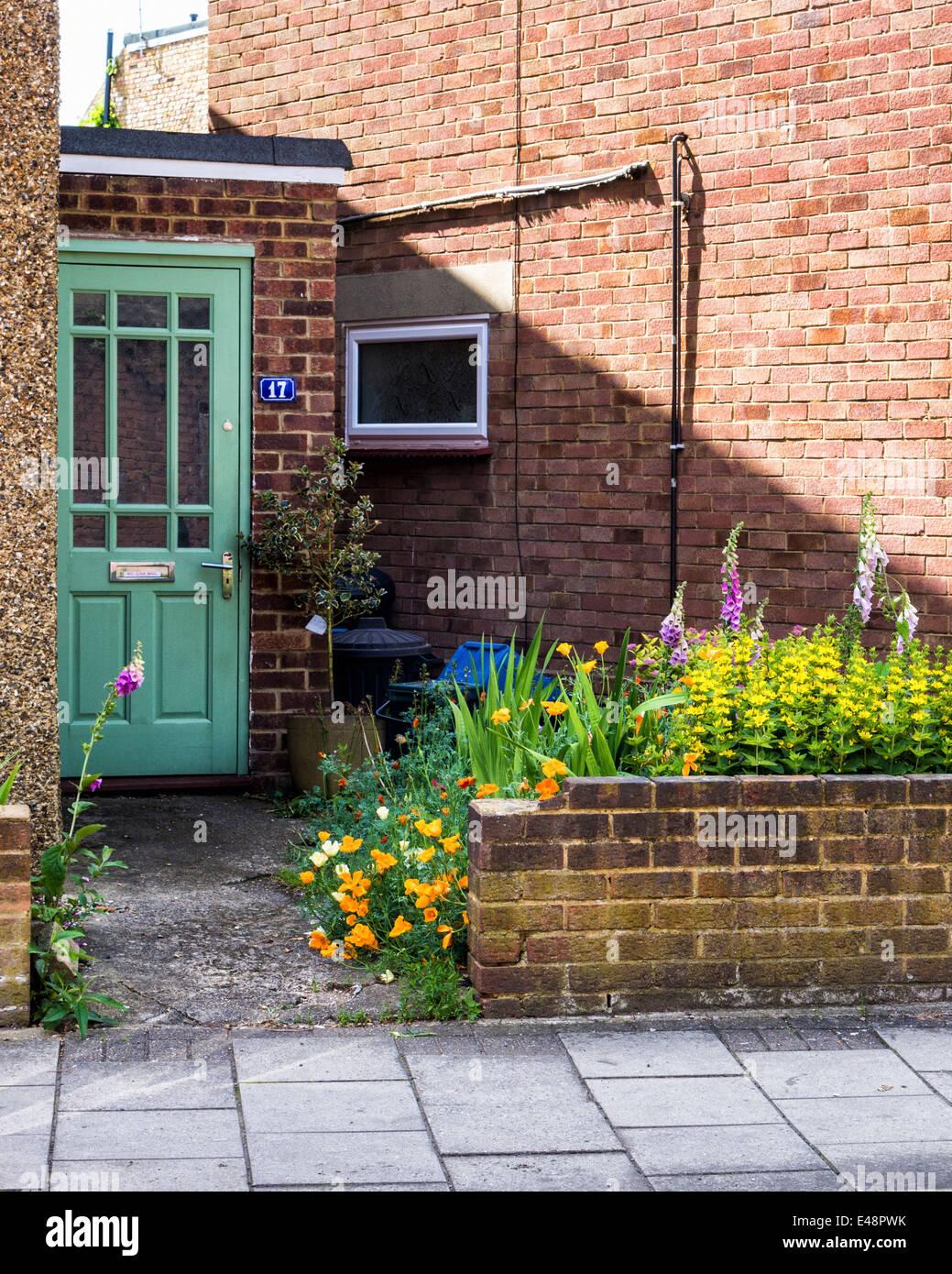 Green door, flowering plants and broken wall of suburban home in Twickenham, London, UK - Stock Image