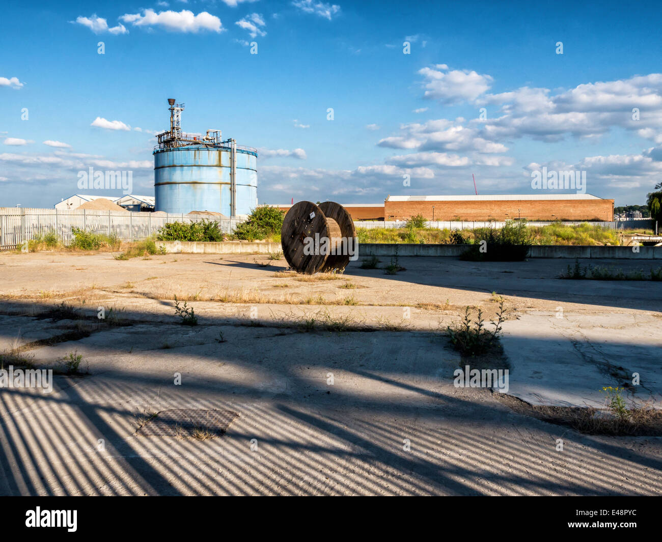 Gas Holder, old cable reel and shadows in an urban wasteland along the Thames Path, Greenwich, London, UK - Stock Image