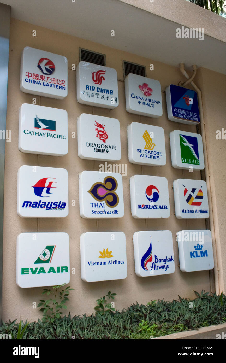 Signs with Asian Airline logos are attached to a wall at a