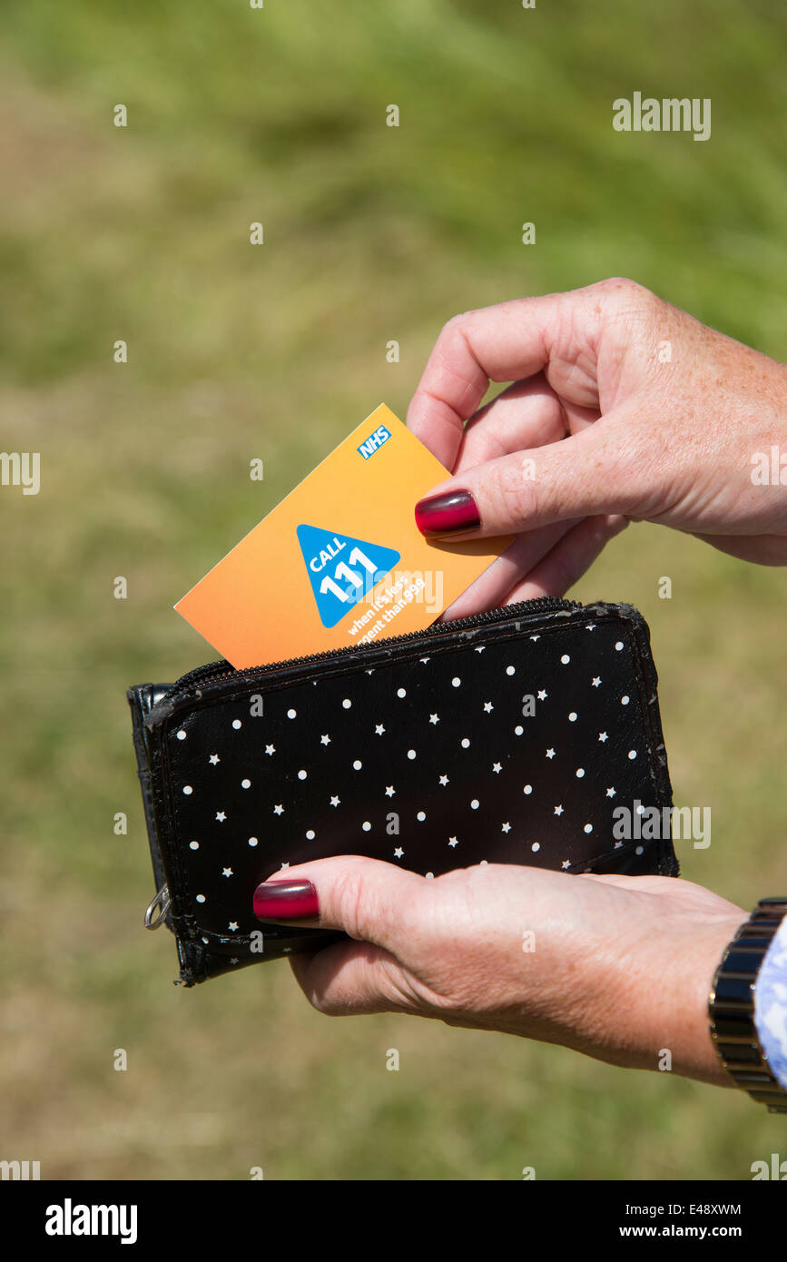 NHS 111 card for use in an emergency Woman taking a card from her purse - Stock Image