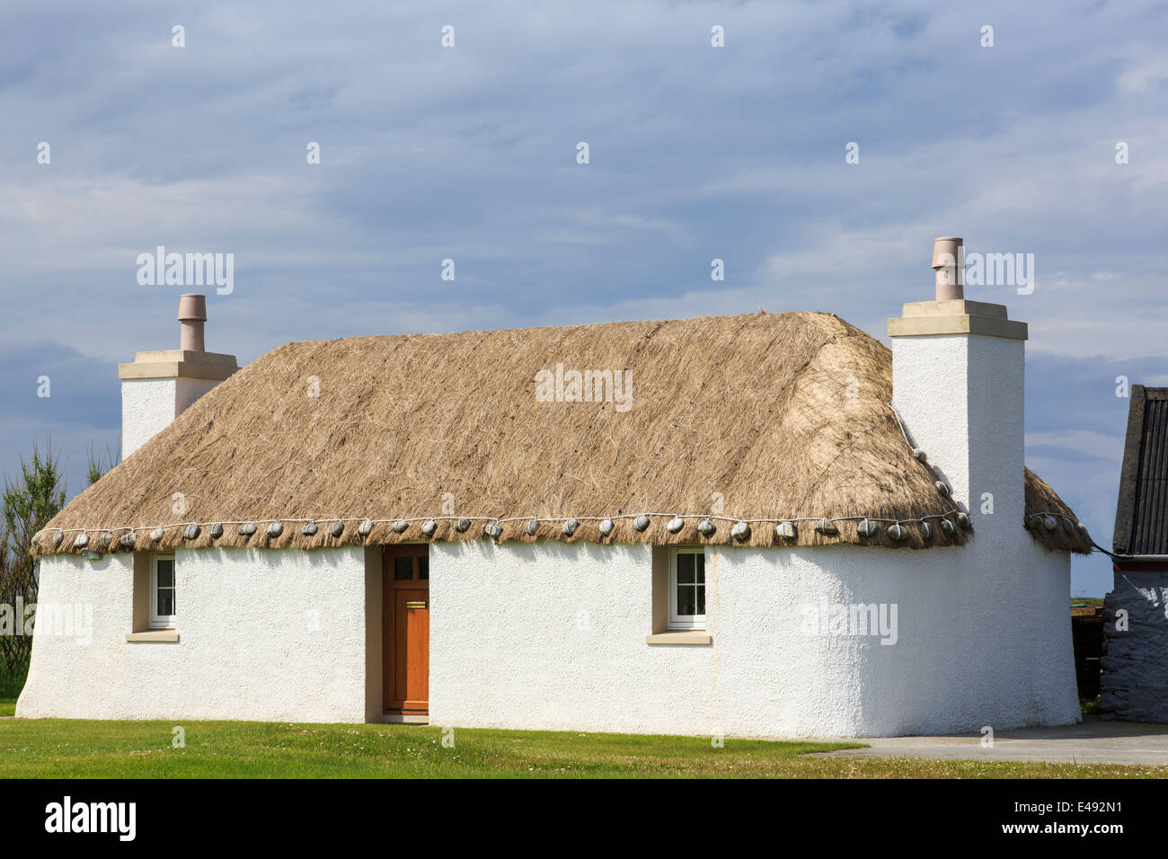 Old restored thatched croft cottage with traditional Scottish limewashed walls. South Uist Outer Hebrides Western - Stock Image