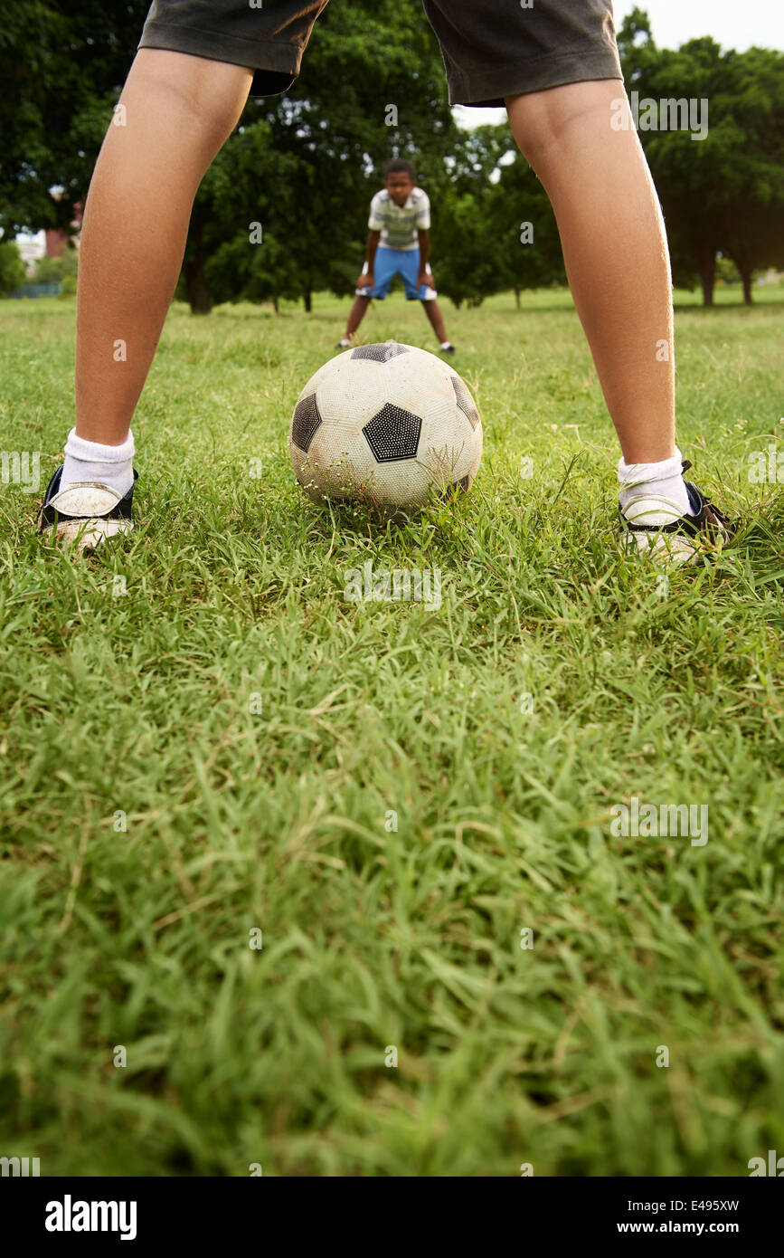 Children playing soccer game in park, with copy space on grass and focus on football ball - Stock Image