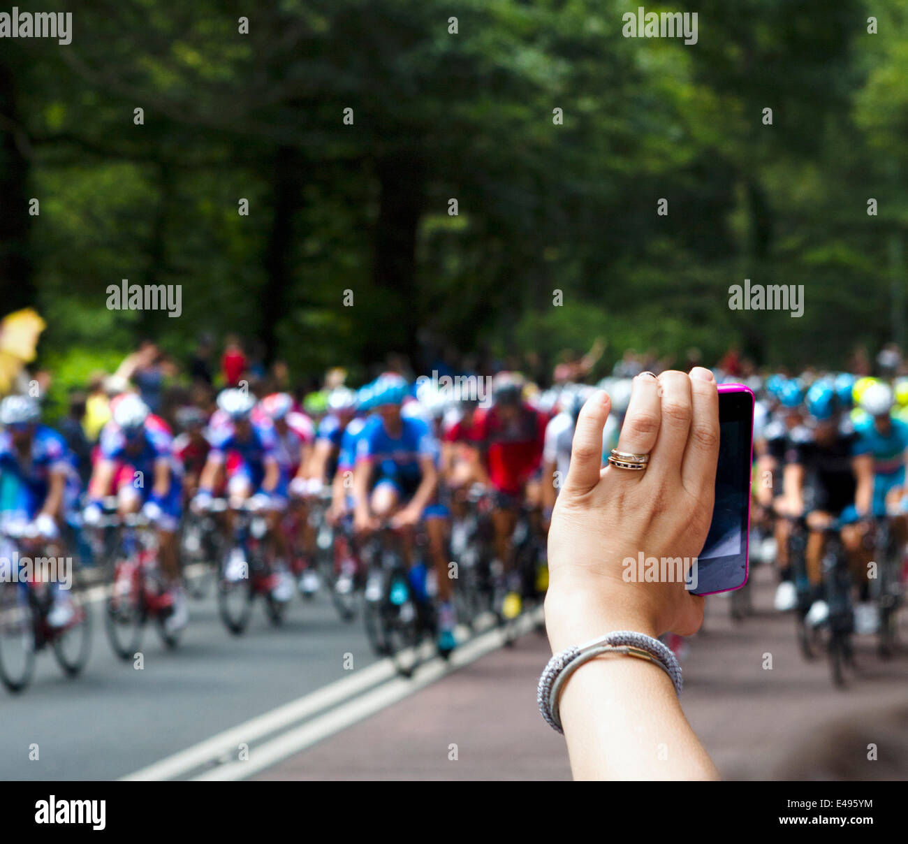 Woman taking a photo with a smartphone of the peleton approaching Holmfirth on Stage 2 of the 2014 Tour de France. - Stock Image