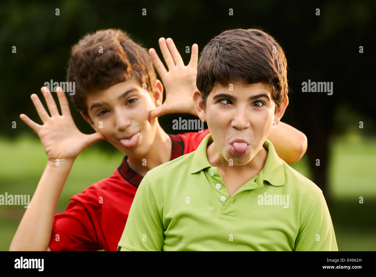 Portrait of happy hispanic children, two brothers, making a face and grimacing at camera outdoors in park - Stock Image