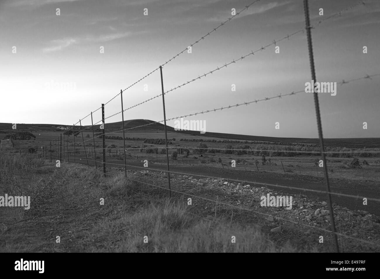 Farmlands as viewed through a barbed wire fence - Stock Image