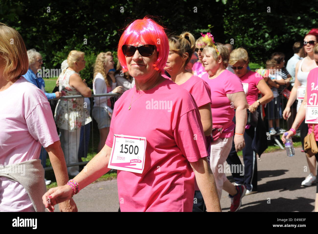 Liverpool, UK. Sunday 6th July 2014. Another woman in a pink wig. Cancer Research UK's Race for Life is a series Stock Photo