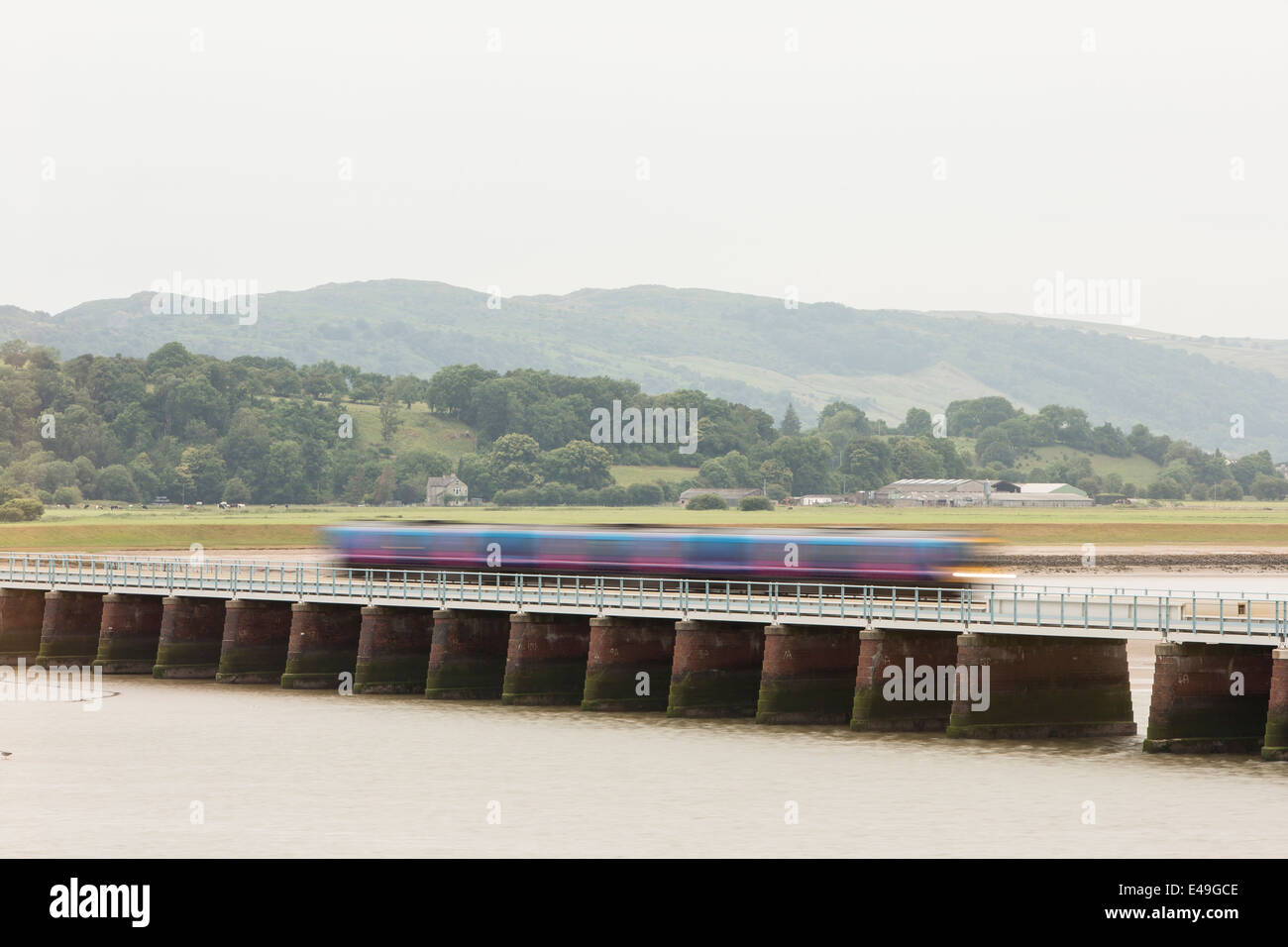 Diesel Multiple Unit (DMU) Class 156 operated by Northern Rail crossing the Kent Viaduct, Cumbria (Long exposure) - Stock Image