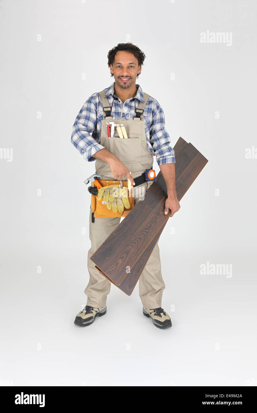 Woodworker pointing to laminate flooring - Stock Image