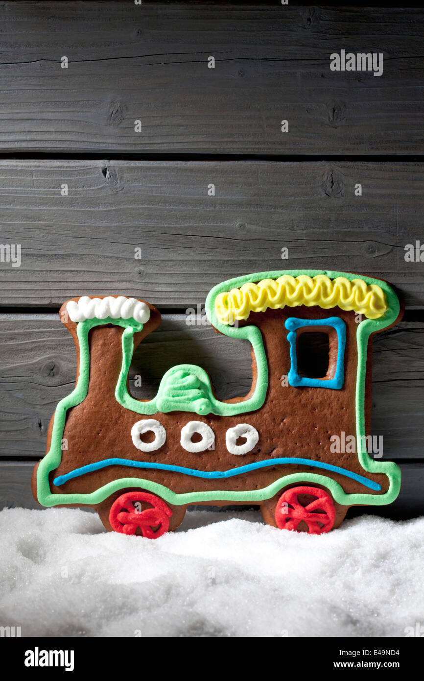 Gingerbread locomotive standing on artificial snow in front of grey wooden wall - Stock Image