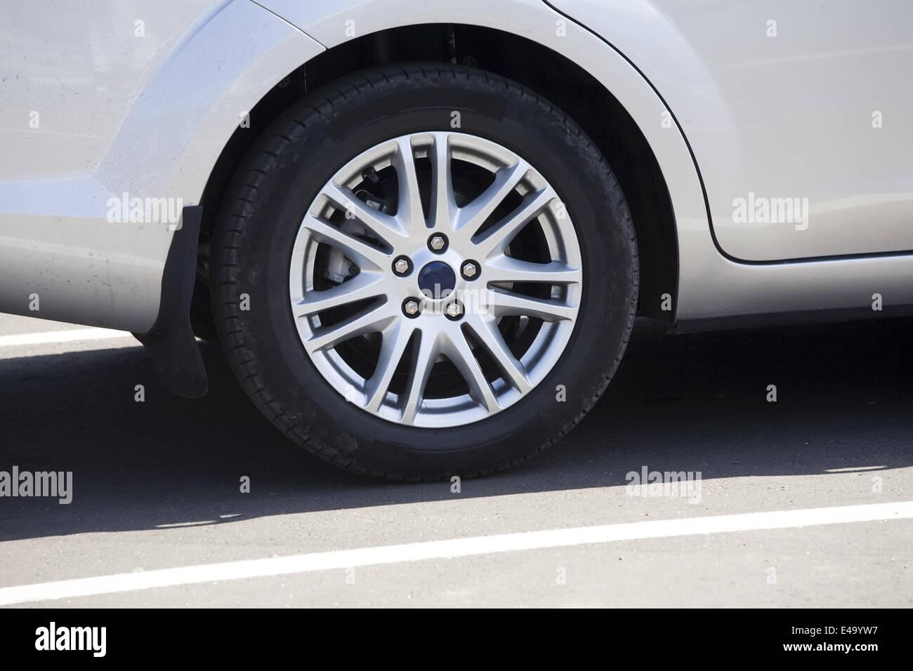 wheel modern passenger car on parking - Stock Image