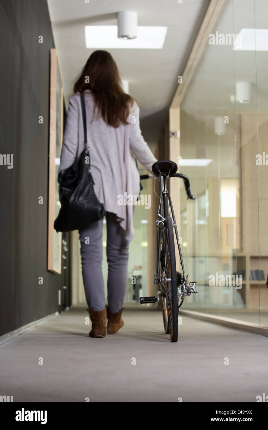 Business woman leaving office with racing cycle - Stock Image