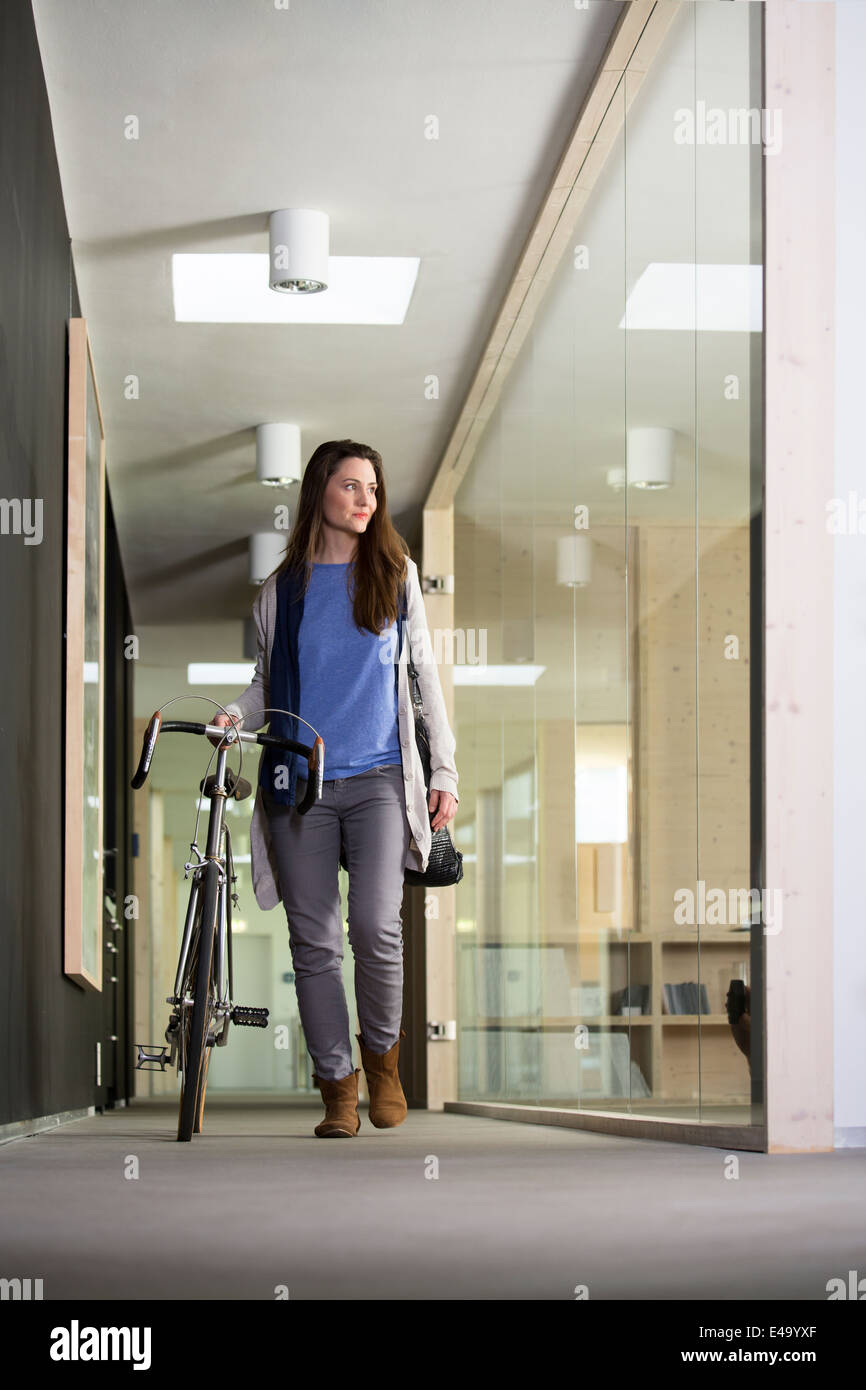 Business woman arriving at office with racing cycle - Stock Image