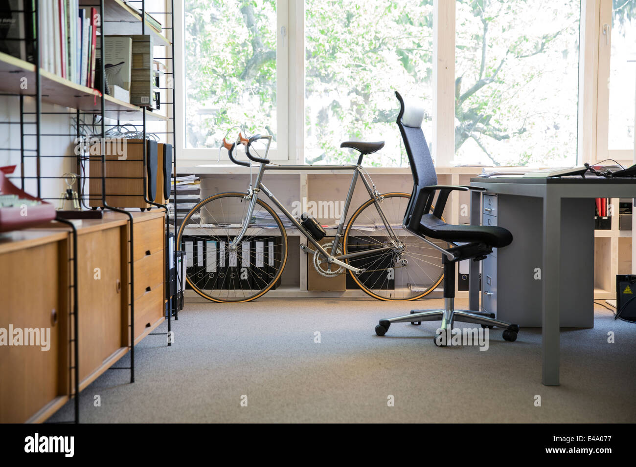 Racing cycle standing at workplace of modern office - Stock Image