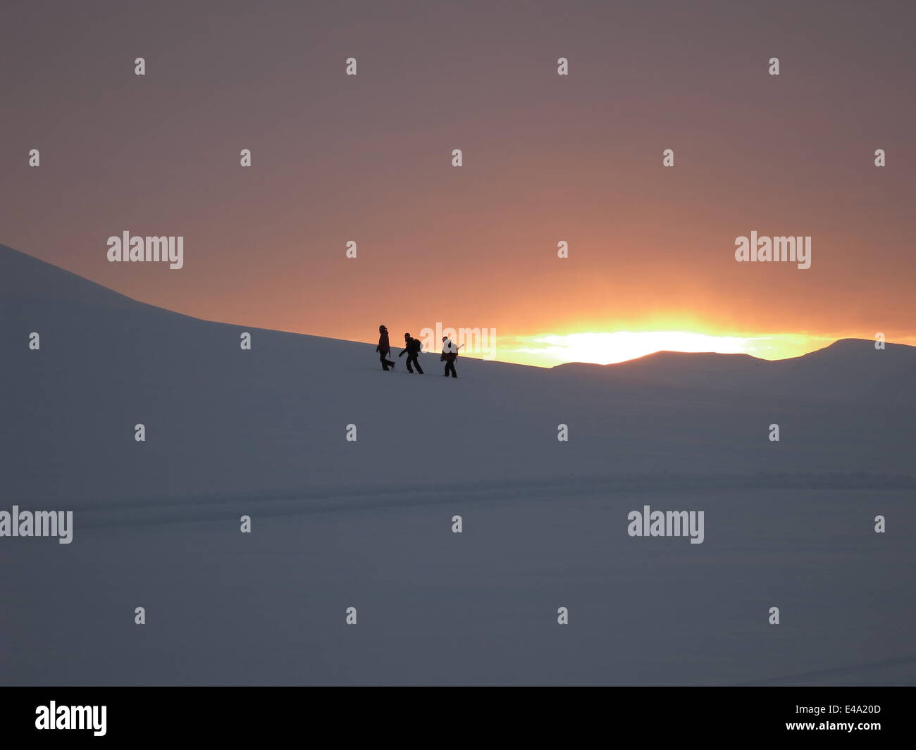 Trekking in winter snow as the sun rises over the mountains after the four month winter dark period, Svalbard, Arctic, - Stock Image