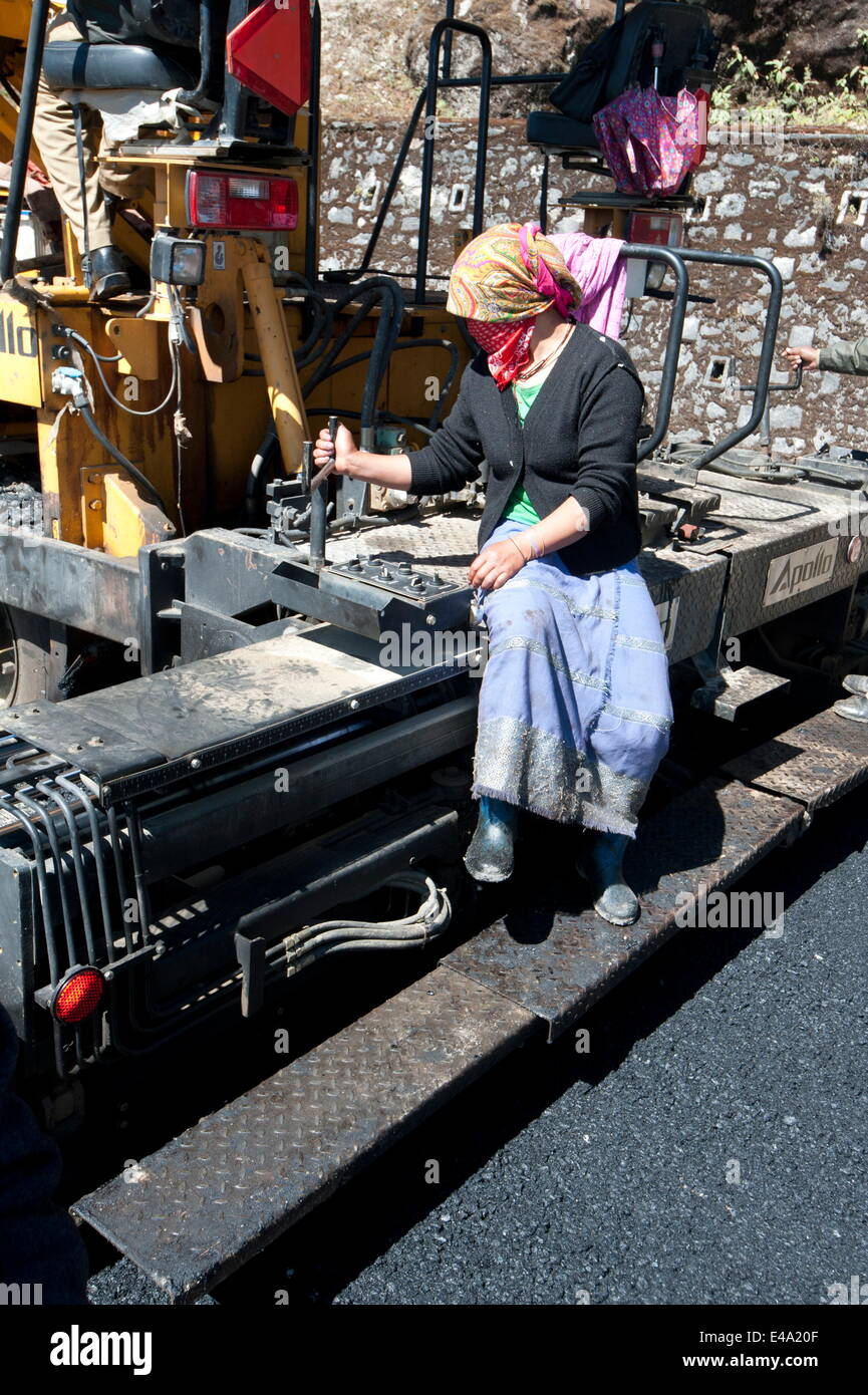 Female road worker in charge of tar spreading machine on hill roads high in Arunachal Pradesh, India, Asia - Stock Image