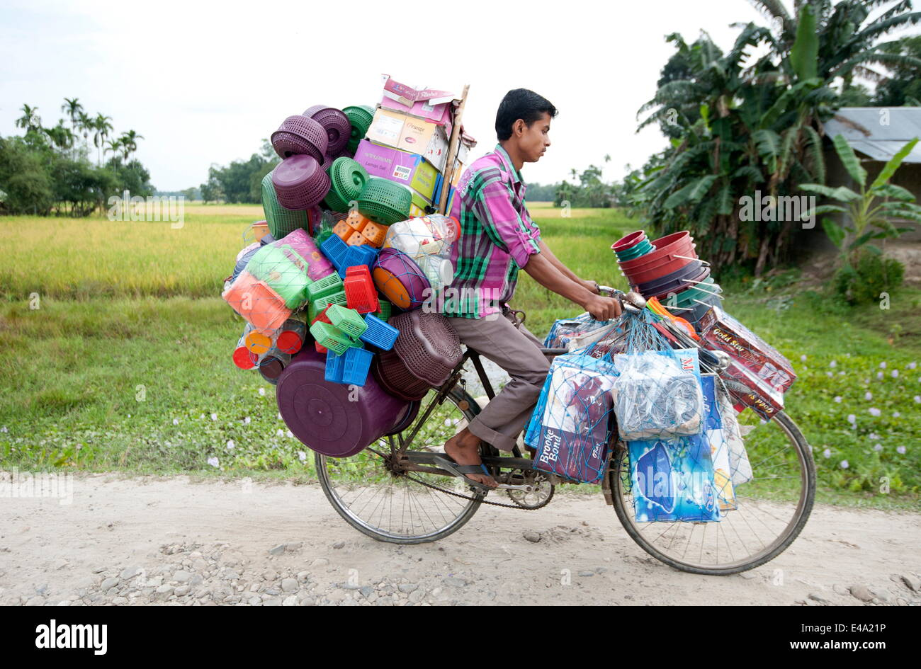 Young village tradesman cycling with a large load of plastic houseware, Majuli, Assam, India, Asia Stock Photo