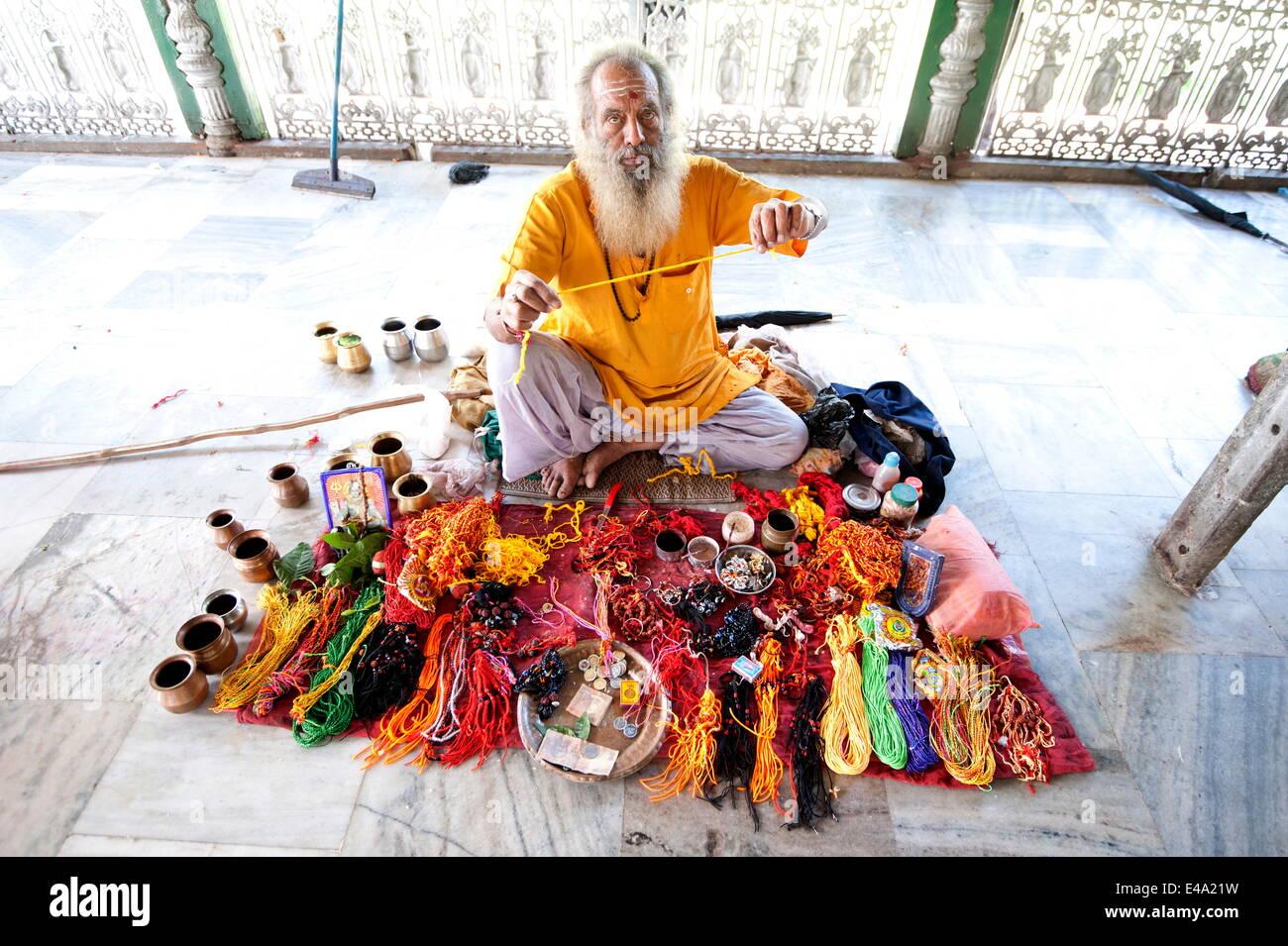 Hindu pundit selling rolimoli (puja wrist threads) in the Sivadol temple, built in 1734, Sivasagar, Assam, India, - Stock Image