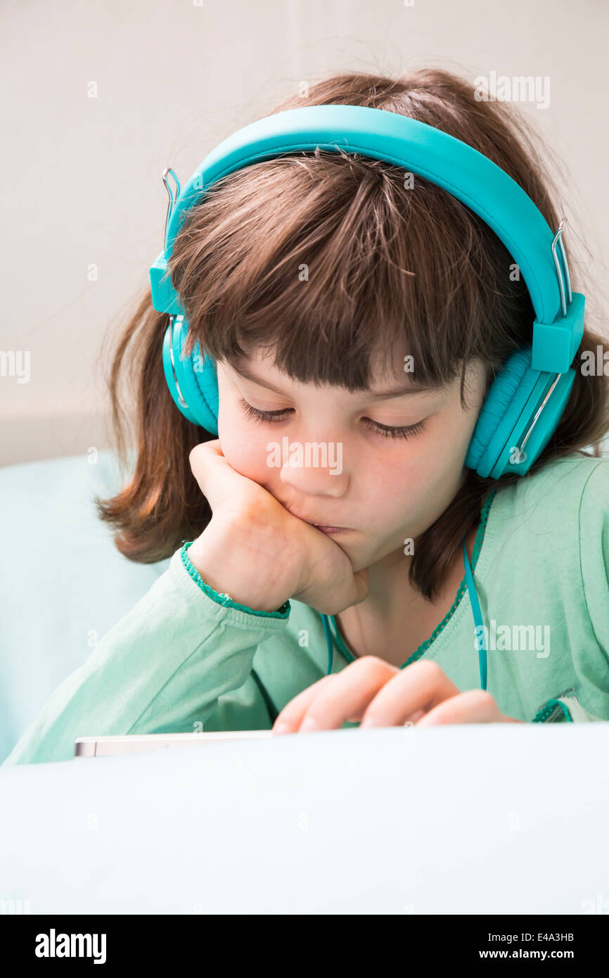 Portrait of little girl with headphones and smartphone - Stock Image