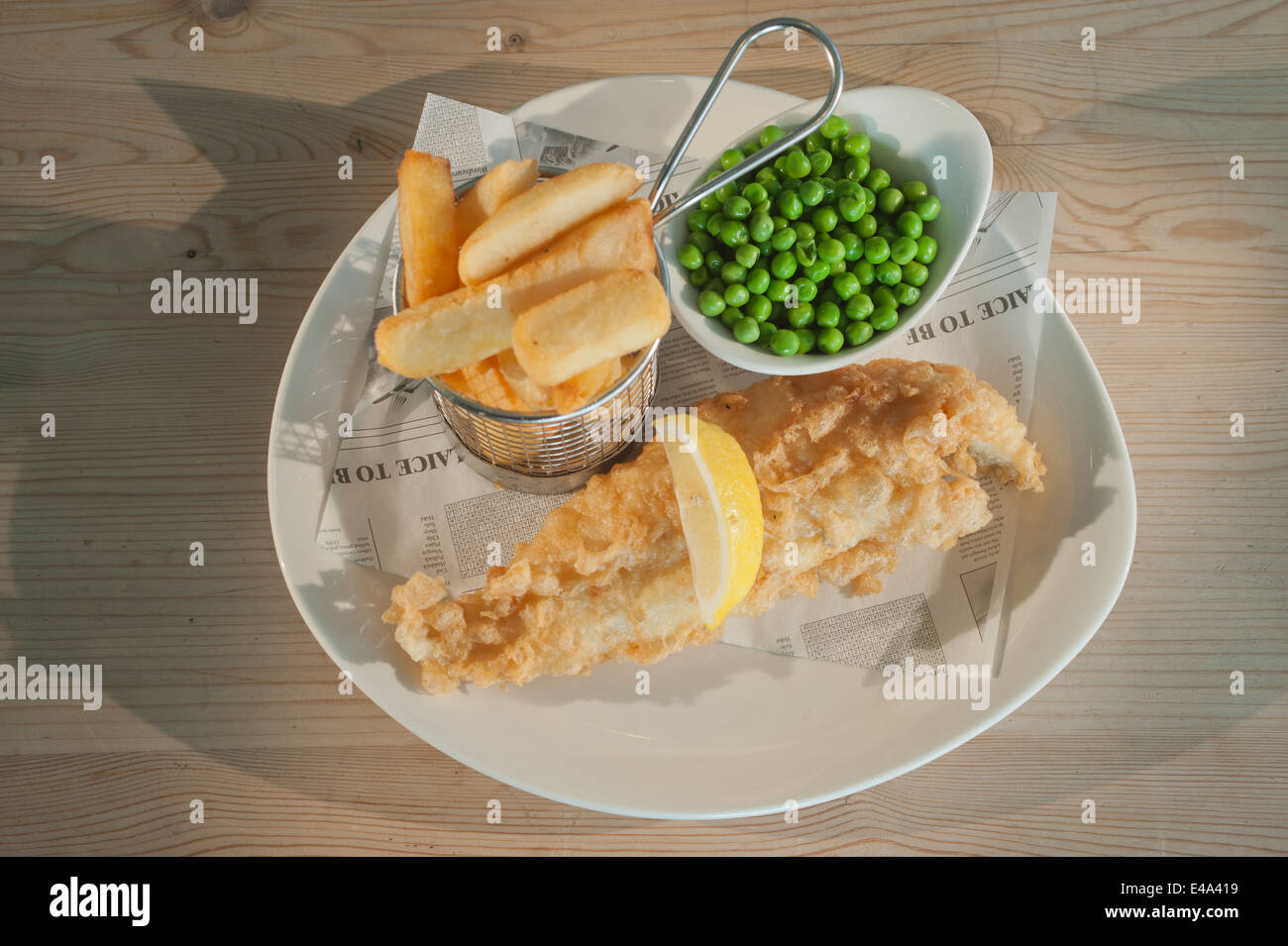 Fish and chips (Haddock in batter) with peas and a segment of lemon on a white plate on a wooden table. - Stock Image