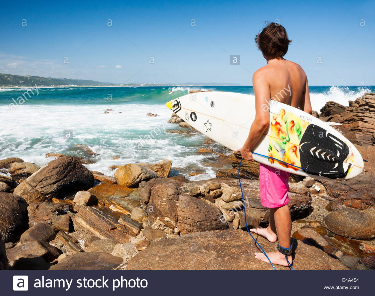 Young adult male with surfboard standing on rocks looking at waves, Victoria Bay Beach, Western Cape, Garden Route, - Stock Image