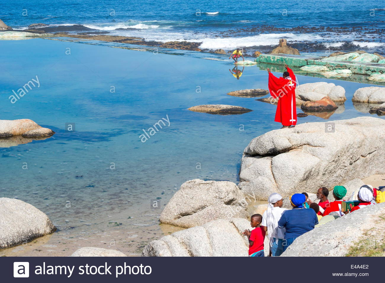 Congregation watches pastor raise his arms to pray before performing water baptism, Atlantic Ocean, Cape Town, South - Stock Image