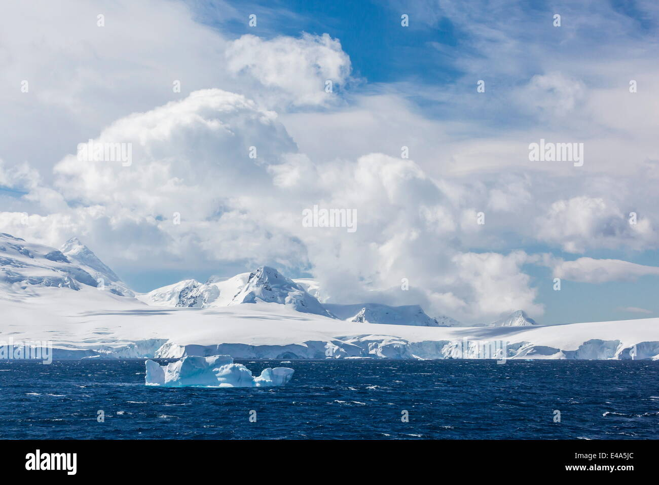 Clouds build over snow-capped mountains in Dallmann Bay, Antarctica, Polar Regions - Stock Image
