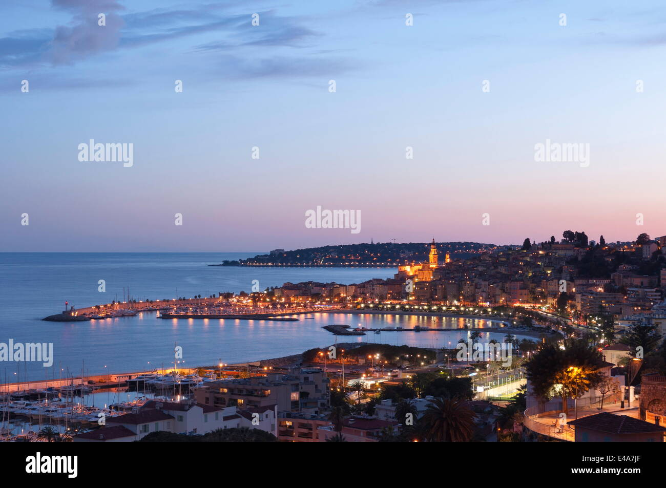 A cityscape of Menton at dusk, Provence-Alpes-Cote d'Azur, French Riviera, France, Mediterranean, Europe - Stock Image