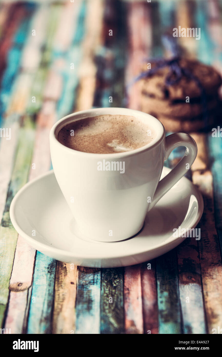 Cup of coffee and chocolate cookies on coloured wood - Stock Image