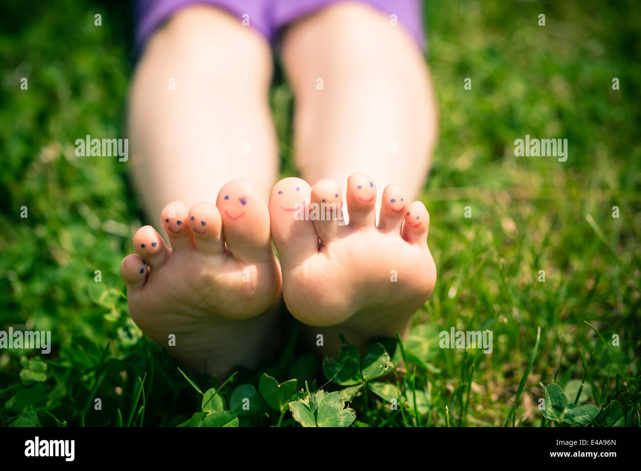 Little girl's feet with painted toes lying in grass - Stock Image