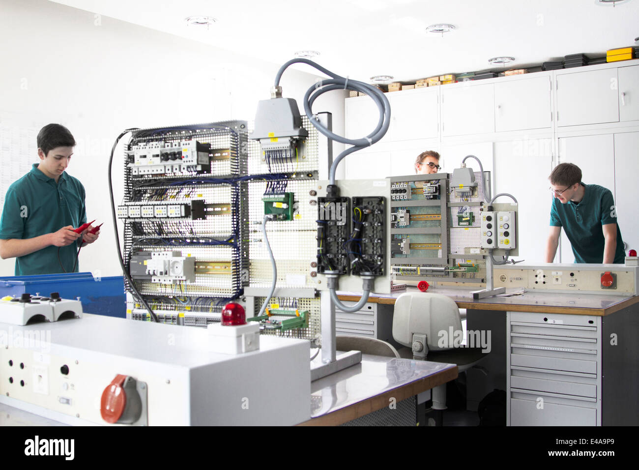 Three electronic apprentices at workshop - Stock Image