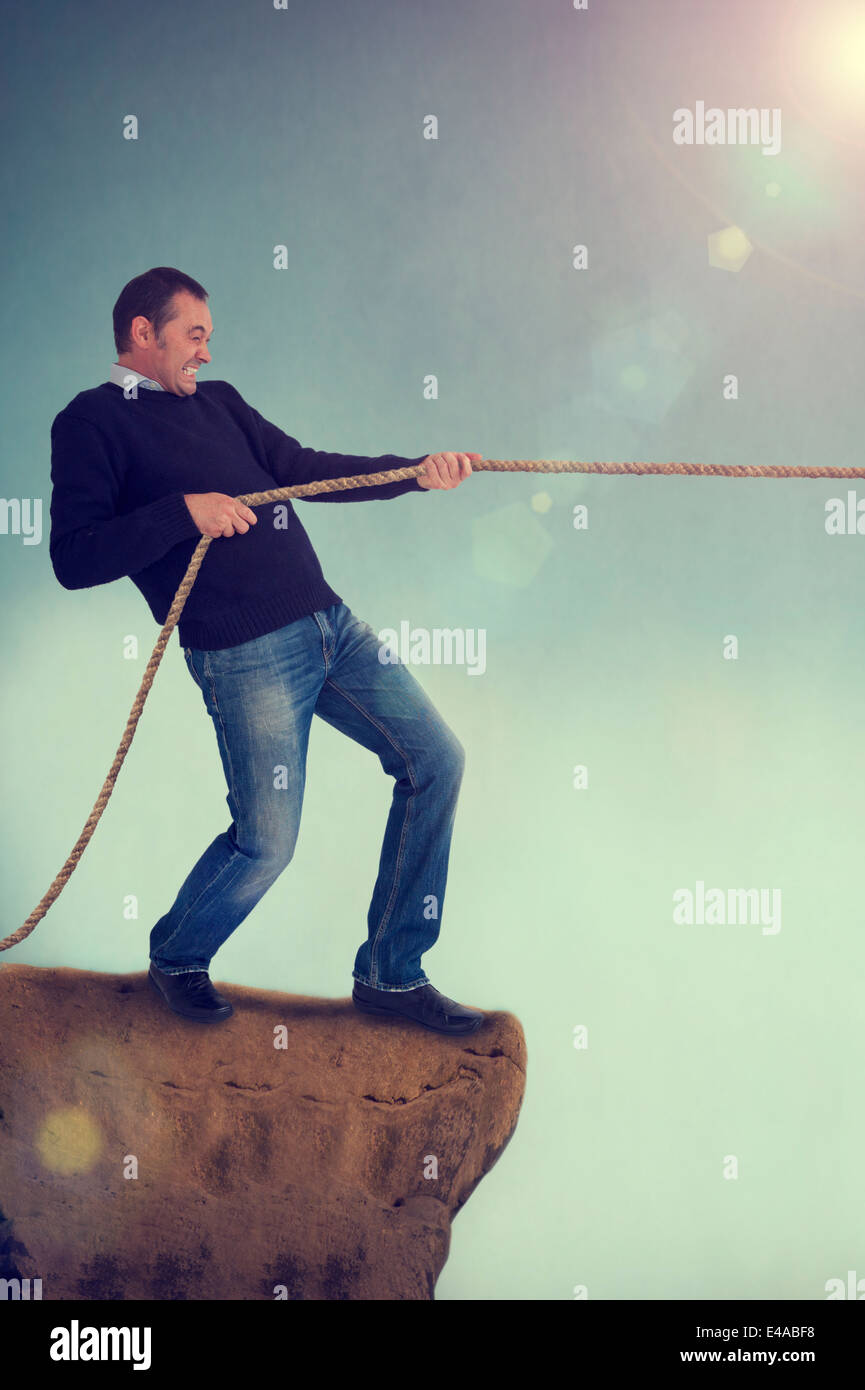 man pulling rope tug of war on a cliff edge adversity concept - Stock Image