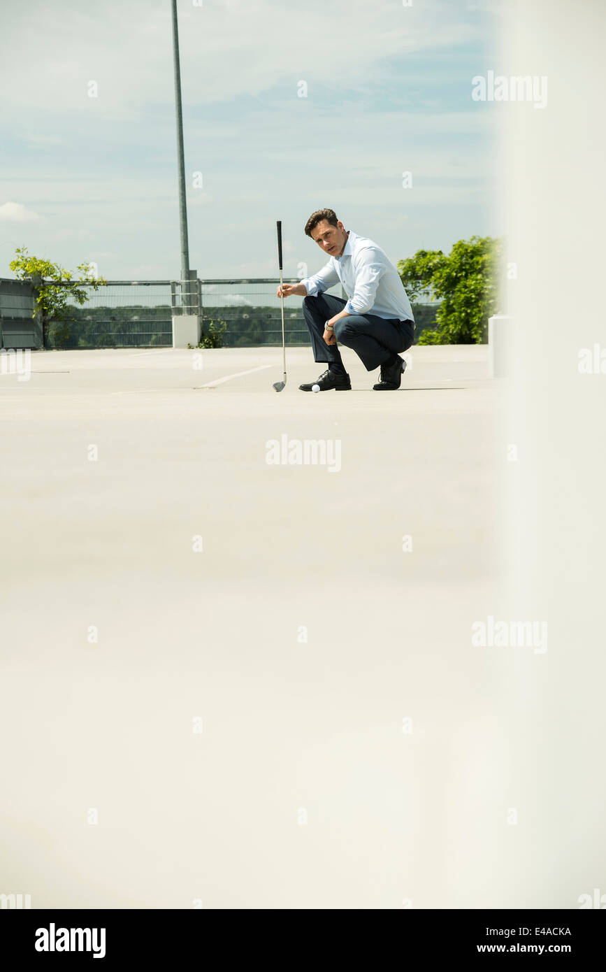 Business man golfing on parking level - Stock Image