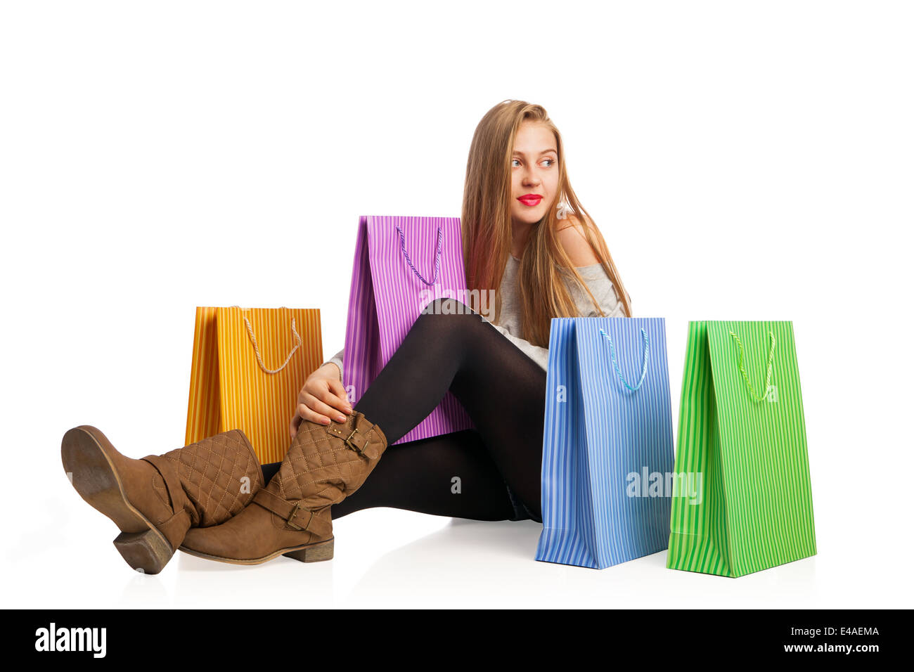 Beautiful excited woman sitting among colorful shopping bags - Stock Image