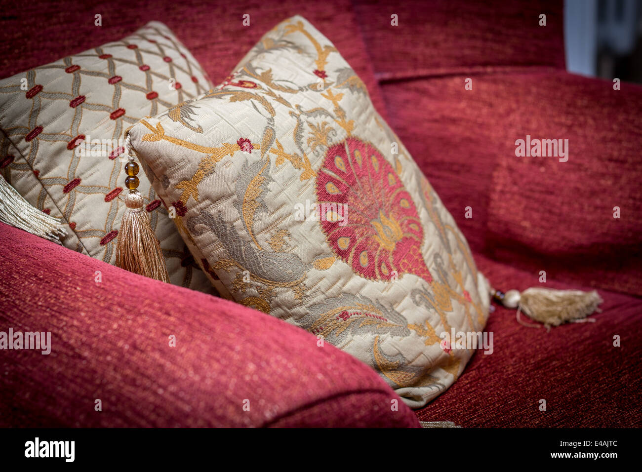 cushions placed on a red armchair - Stock Image