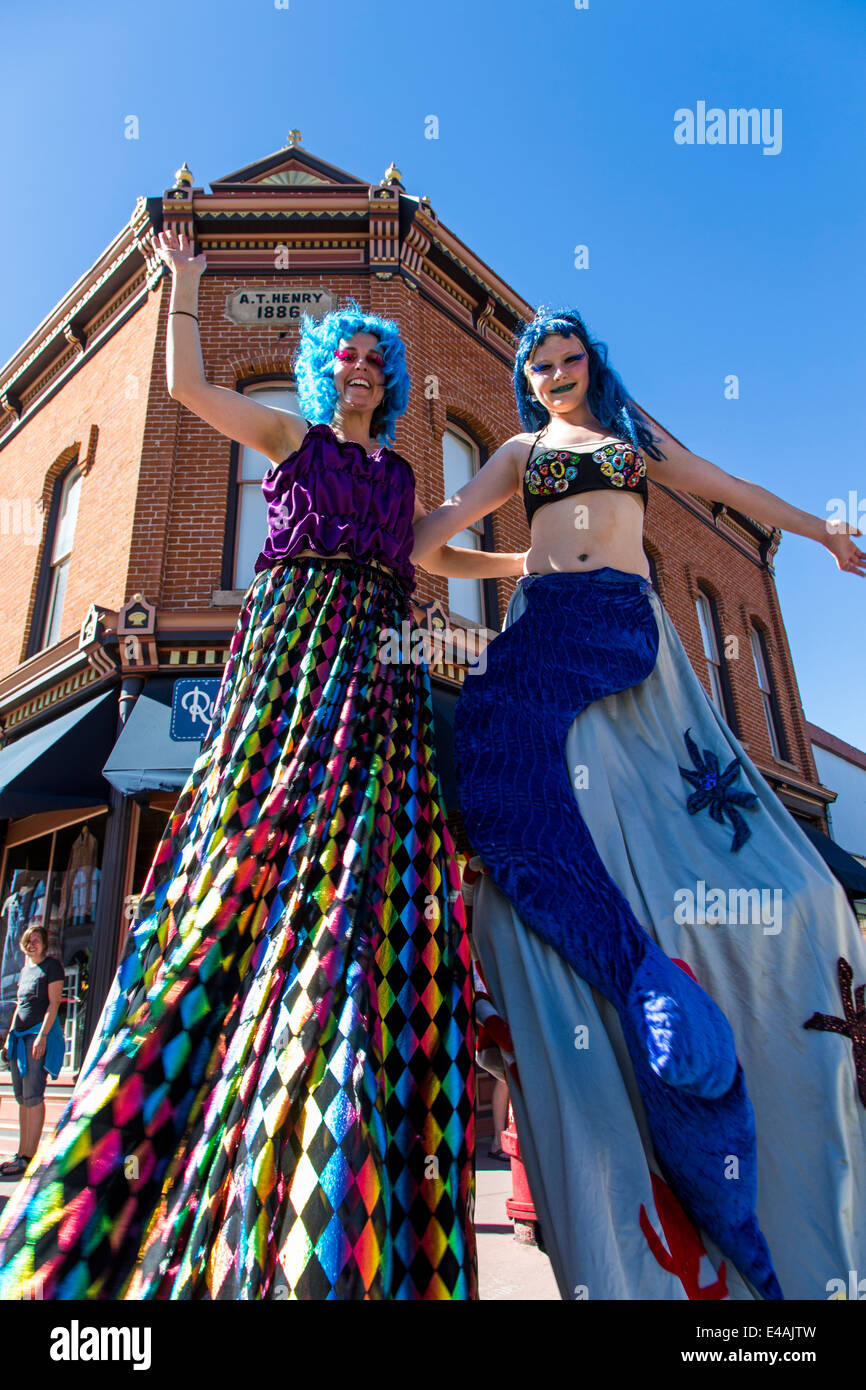 Circus performers on stilts entertain visitors enjoying artwork during the annual small town ArtWalk Festival Stock Photo