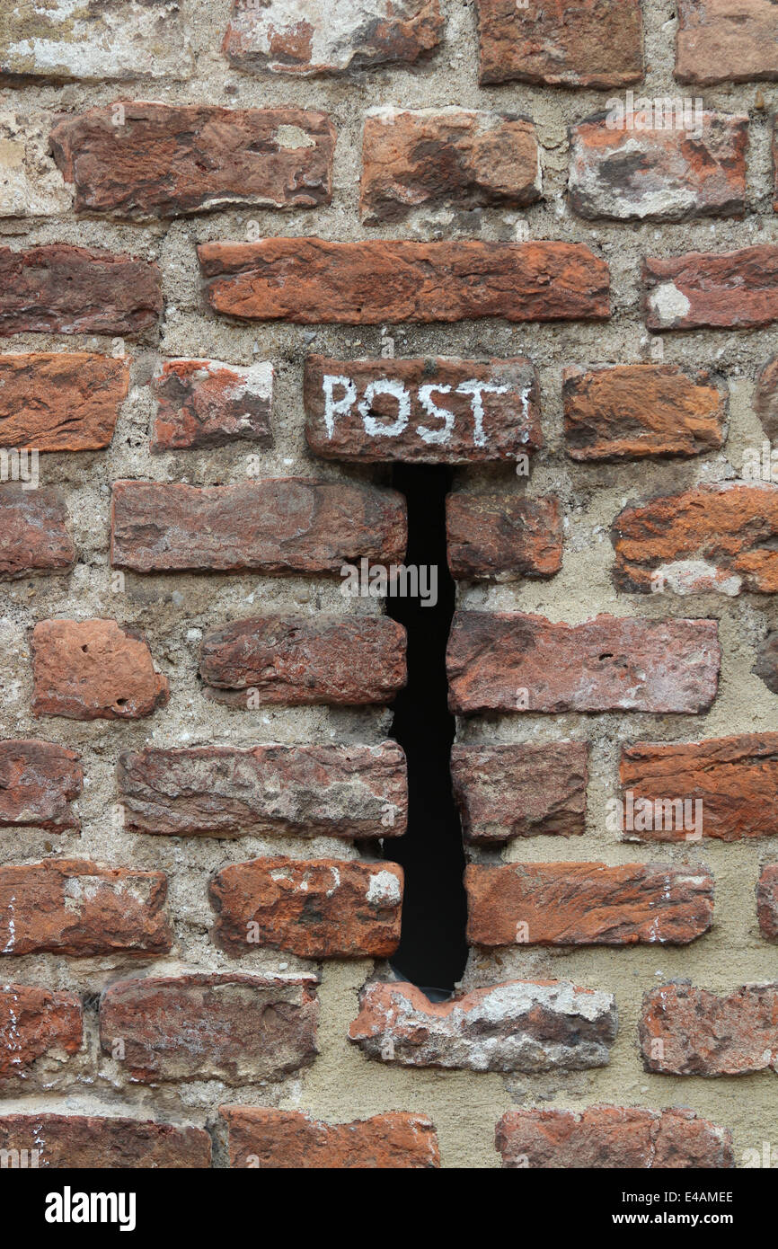 gun slots in brick house converted to mail slot Stock Photo