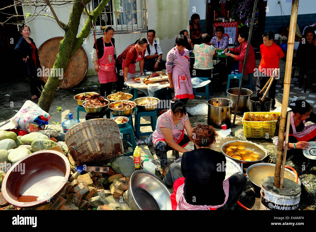PENGZHOU, CHINA: A large gathering of people with copious amounts of food for an outdoor wedding luncheon Stock Photo