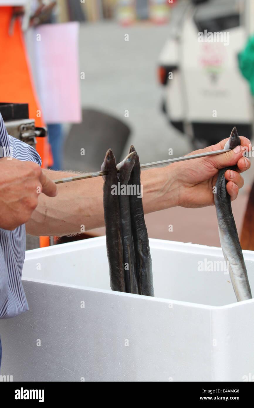 Man preparing smoked eels Stock Photo