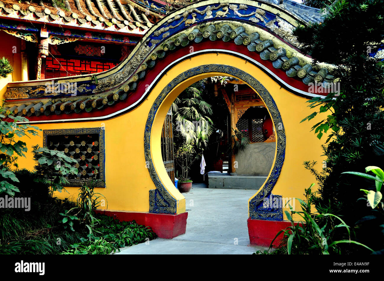 PENGZHOU, CHINA: A moon gate flanked by gardens leads into an inner courtyard at the Ci Ji Buddhist Temple - Stock Image