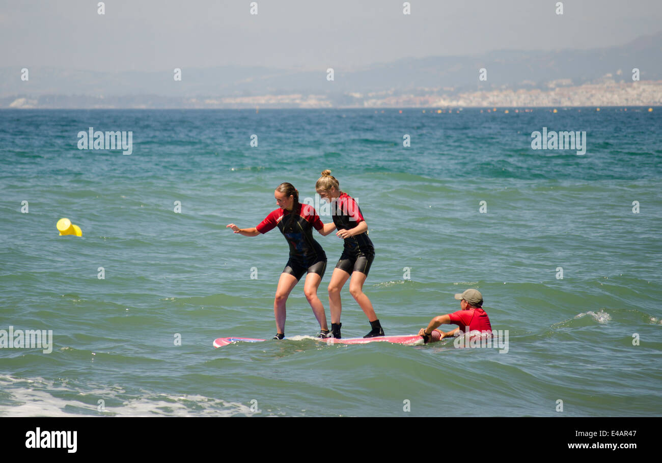Two girls getting lessons at a surf school, on beach in Marbella, Spain. - Stock Image